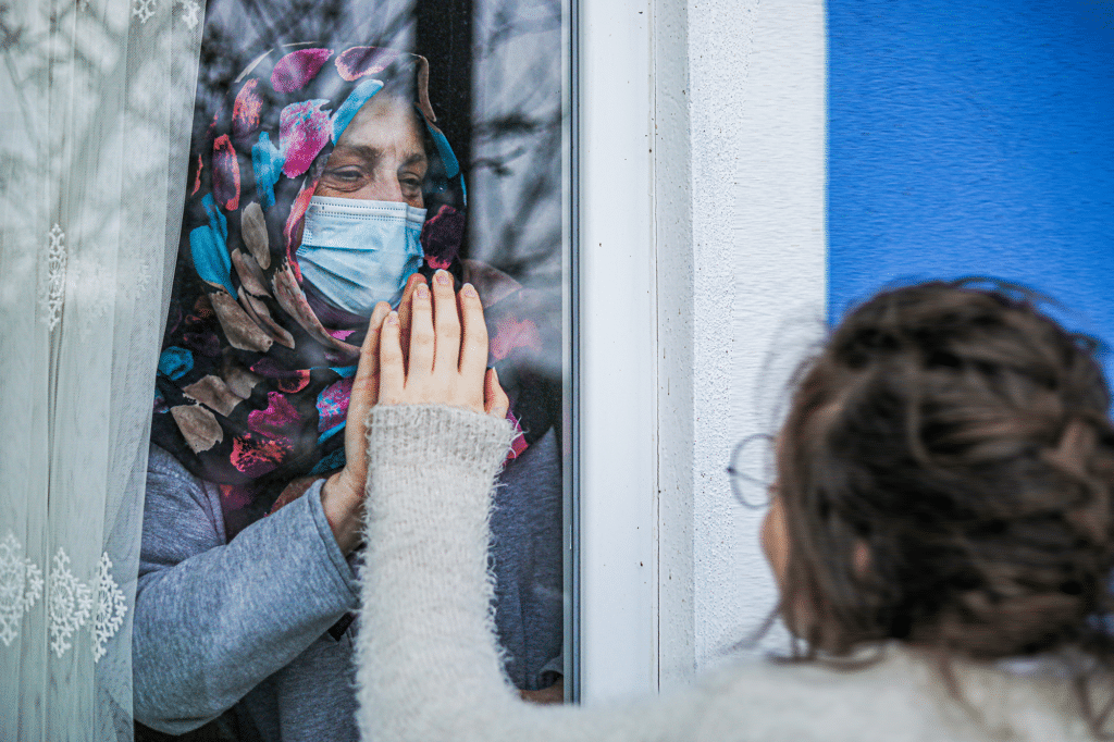 Woman in Quarantine With Her Child Holding Hands Behind The Window