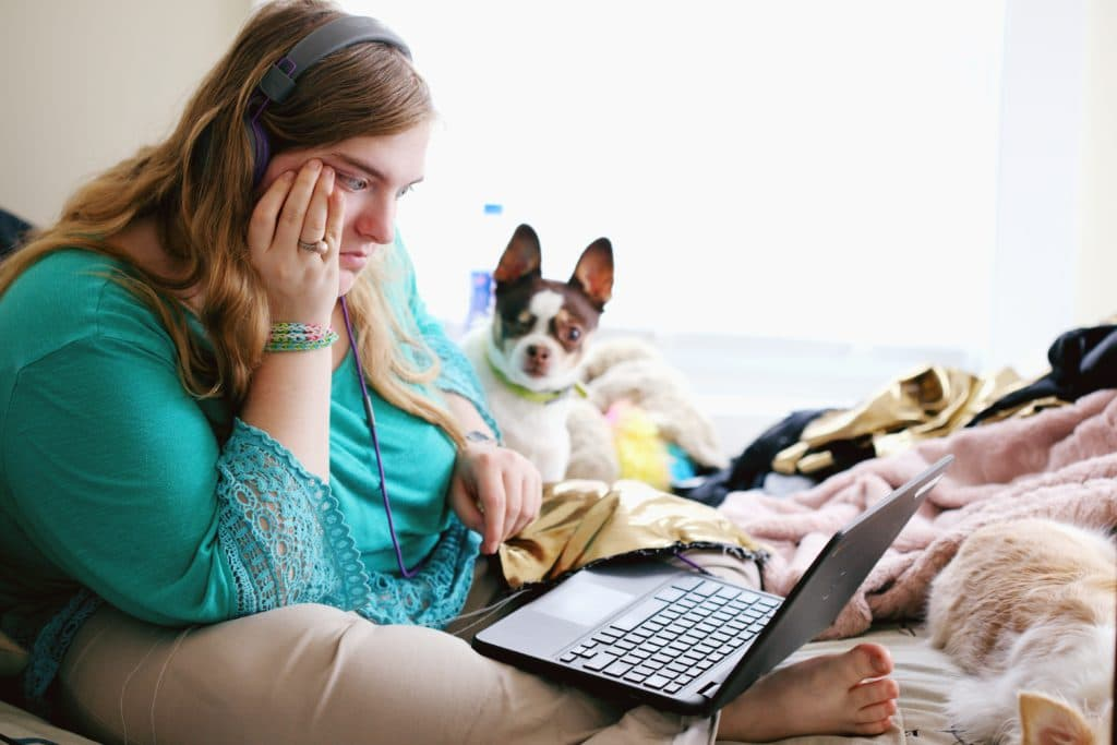 Young woman with autism and other learning disabilities using laptop for remote learning.